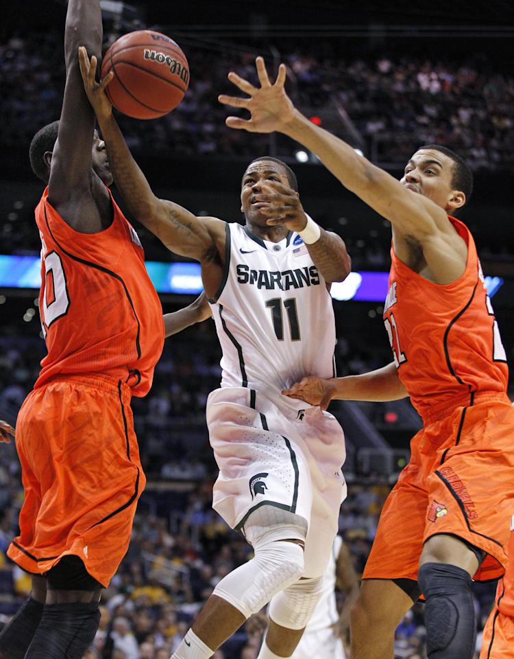 Michigan State's Keith Appling (11) drives between Louisville defenders Gorgui Dieng, left, and Elisha Justice during the first half of an NCAA men's college basketball tournament West Regional semifinal on Thursday, March 22, 2012, in Phoenix. (AP Photo/Chris Carlson)