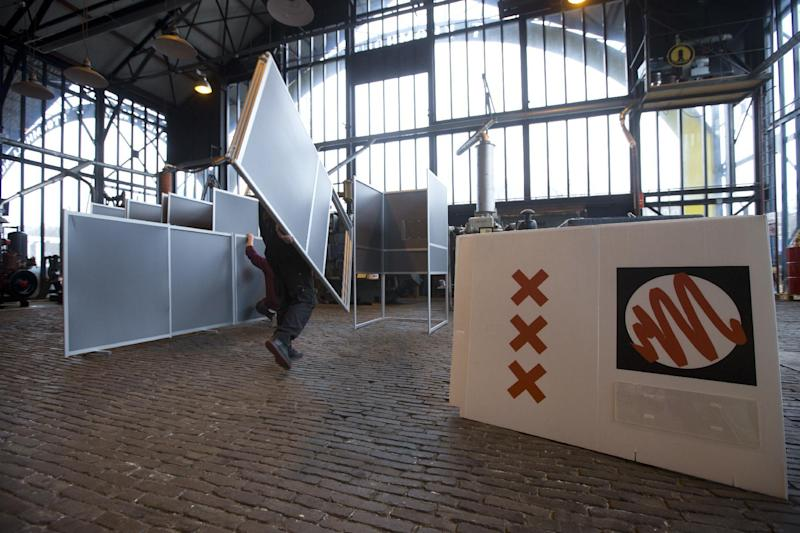 Workers set up a polling station at 'T Kromhout museum for maritime engines and shipyard in Amsterdam, Netherlands, Tuesday, March 14, 2017. Amid unprecedented international attention, the Dutch go to the polls Wednesday in a parliamentary election that is seen as a bellwether for the future of populism in a year of crucial votes in Europe. The placard with the voting sign also carries the three crosses of the city of Amsterdam. (AP Photo/Peter Dejong)
