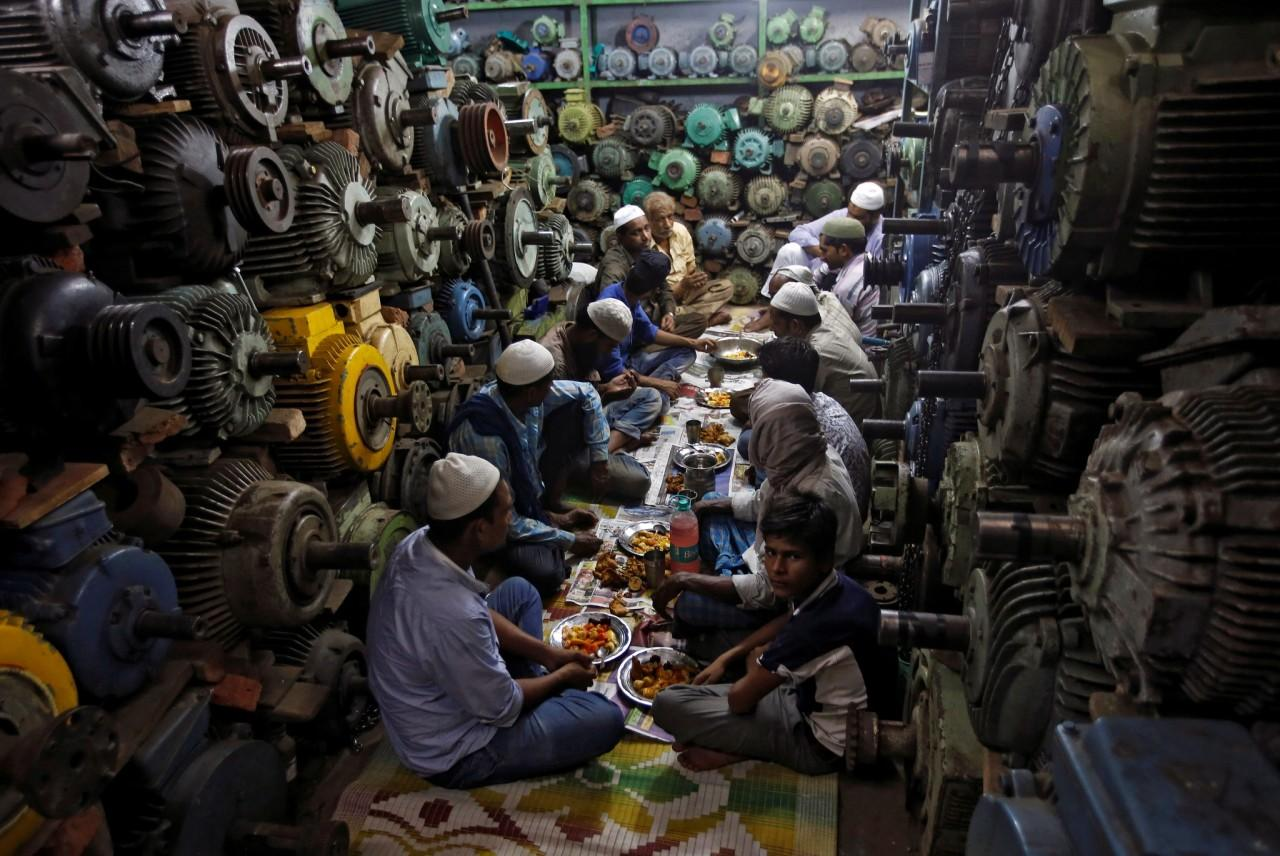 <p>Muslims eat their iftar (breaking of fast) meal at a water pump workshop in the old quarters of Delhi, India, June 8, 2016. (Adnan Abidi/Reuters) </p>