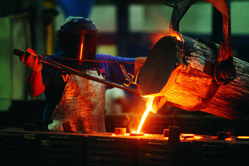 A person pouring molten steel in a foundry.