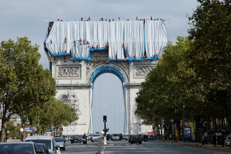 Workers unravel fabric over L'Arc de Triomphe in Paris, part of a project by the late artist Christo (AFP/Thomas SAMSON)