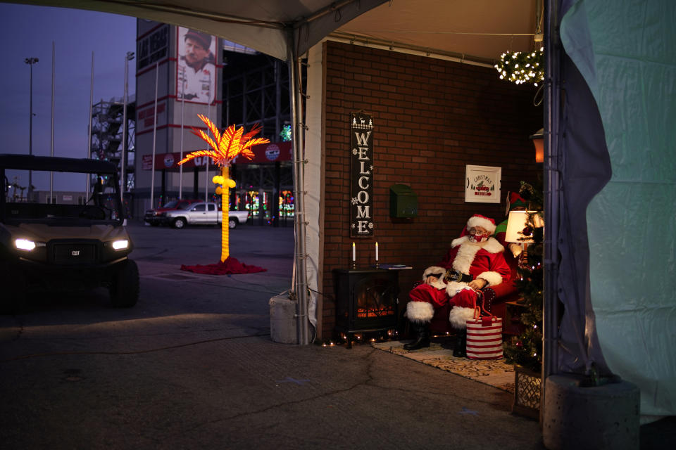 Bill Sandeen, dressed as Santa Claus, waits for cars at a drive-thru Santa selfie station at Glittering Lights, a drive-thru holiday lights display in Las Vegas, on Dec. 11, 2020. In this socially distant holiday season, Santa Claus is still coming to towns (and shopping malls) across America but with a few 2020 rules in effect. (AP Photo/John Locher)