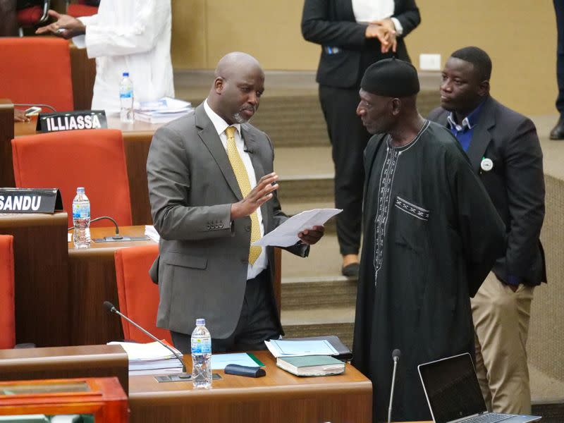 The Gambia Justice Minister Abubacarr Tambadou discusses the bill with a member of Parliament at the national assembly in  Banjul