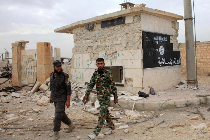 """Syrian government forces walk past a building bearing an image on the wall reading in Arabic the """"Islamic State"""" in the village of Jabboul on the eastern outskirts of the northern Syrian city of Aleppo on October 24, 2015 (AFP Photo/George Ourfalian)"""