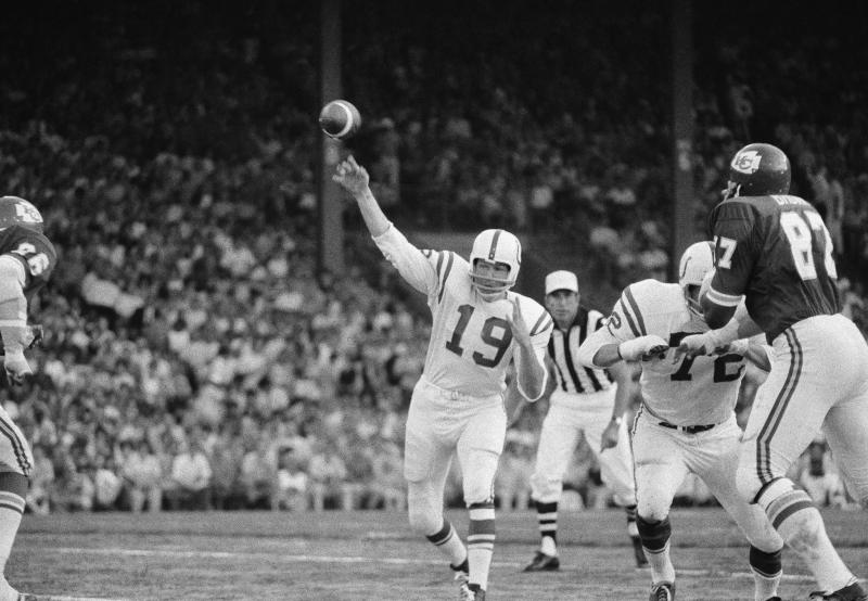 File-This Aug. 15, 1970, file photo shows  Baltimore Colts quarterback Johnny Unitas (19) getting off a pass as left tackle Bob Vogel (72) keeps Kansas City's Aaron Brown away in the exhibition game at Kansas City. Members of a special panel of 26 selected all of them for the position as part of the NFL's celebration of its 100th season. All won league titles except Marino. All are in the Hall of Fame except Brady and Manning, who are not yet eligible.  On Friday, Dec. 27, 2019, quarterback was the final position revealed for the All-Time Team.  (AP Photo/William Straeter, File)