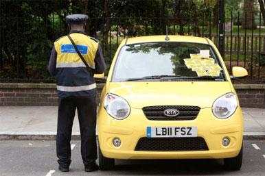 traffic warden and car with numerous parking tickets