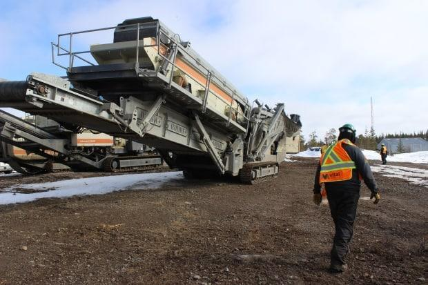 Kyle Bayha, an employee at the Nechalacho rare earths mine demonstration project, pictured on Thursday. He walks past a crusher that'll be used to break down ore. (Liny Lamberink/CBC North - image credit)