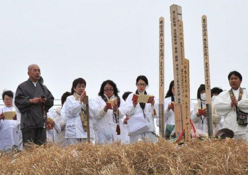 Believers pray for victims of 2011's massive earthquake and tsunami at a memorial on March 8