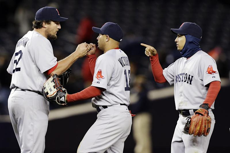 Boston Red Sox right fielder Shane Victorino (18) and shortstop Jose Iglesias (10) celebrate with relief pitcher Joel Hanrahan (52) after their 7-4 win over the New York Yankees in a baseball game at Yankee Stadium in New York, Wednesday, April 3, 2013. (AP Photo/Kathy Willens)