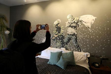 A visitor takes pictures for graffiti work painted by street artist Banksy showing an Israeli soldier and masked Palestinian youth having a pillow fight, in the Walled Off hotel in the West Bank city of Bethlehem March 3, 2017. REUTERS/Ammar Awad