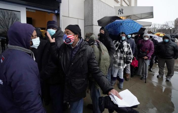 """<div class=""""inline-image__caption""""><p>People line up in the rain outside the Yankee Stadium for vaccinations reserved for residents of The Bronx.</p></div> <div class=""""inline-image__credit"""">Timothy A. Clary/Getty</div>"""