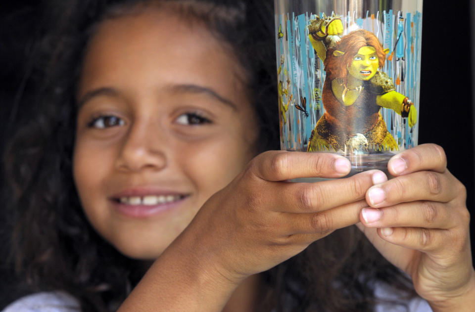 Jasmine Matta, 7, holds up a Shrek-themed glass distributed in McDonald's Happy Meals featuring her favorite character, Fiona, at home on Friday, June 4, 2010, in West Hollywood, Calif.  (AP Photo/Adam Lau)