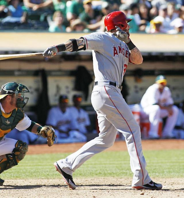 Los Angeles Angels' Josh Hamilton hits a game winning sacrifice fly against the Oakland Athletics during the eleventh inning of a baseball game, Wednesday, Sept. 18, 2013, in Oakland, Calif. The Angels beat the Athletics 5-4 in eleven innings. (AP Photo/George Nikitin)