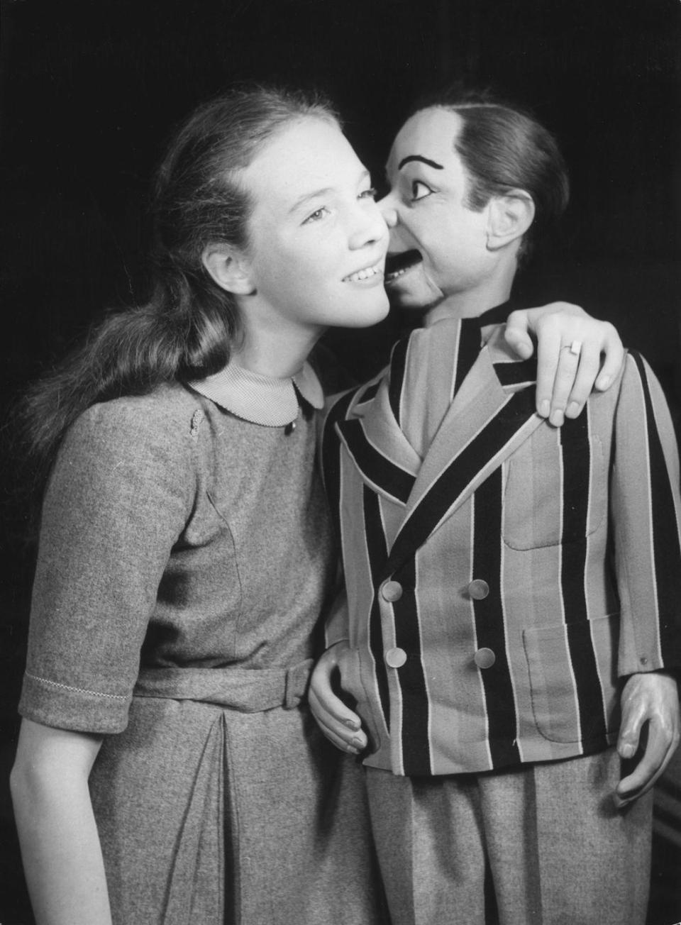 <p>Schoolboy Archie Andrews, the dummy of ventriloquist Peter Brough, whispers in Julie Andrews' ear. </p>