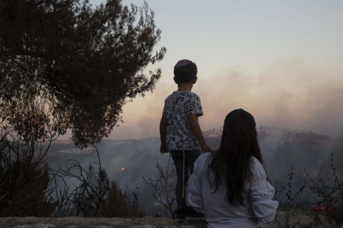 An Israeli mother and son watch from an overlook as firefighters battle wildfires for the second day near Shoresh, on the outskirts of Jerusalem, Monday, Aug. 16, 2021. Israel Fire and Rescue service said in a statement that 45 firefighting teams accompanied by eight planes were working to contain five fires in the forested hills west of the city. (AP Photo/Maya Alleruzzo)