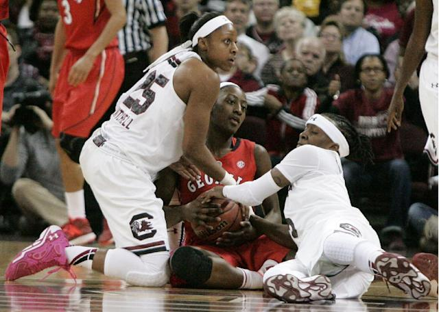 South Carolina's Tiffany Mitchell, left, and Khadijah Sessions, right, try to take the ball from Georgia's Erika Ford (31) during the first half of an NCAA college basketball game Thursday, Feb. 27, 2014, in Columbia, S.C. (AP Photo/Mary Ann Chastain)