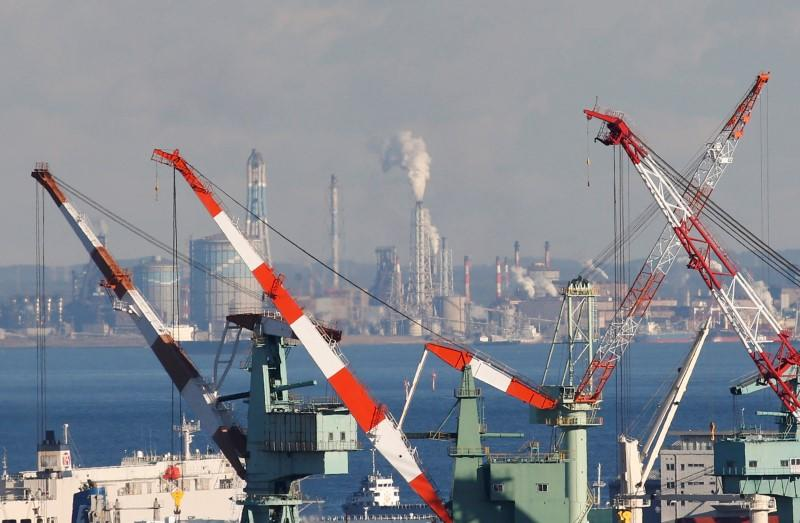 Chimneys and cranes are seen at an industrial area in Yokohama