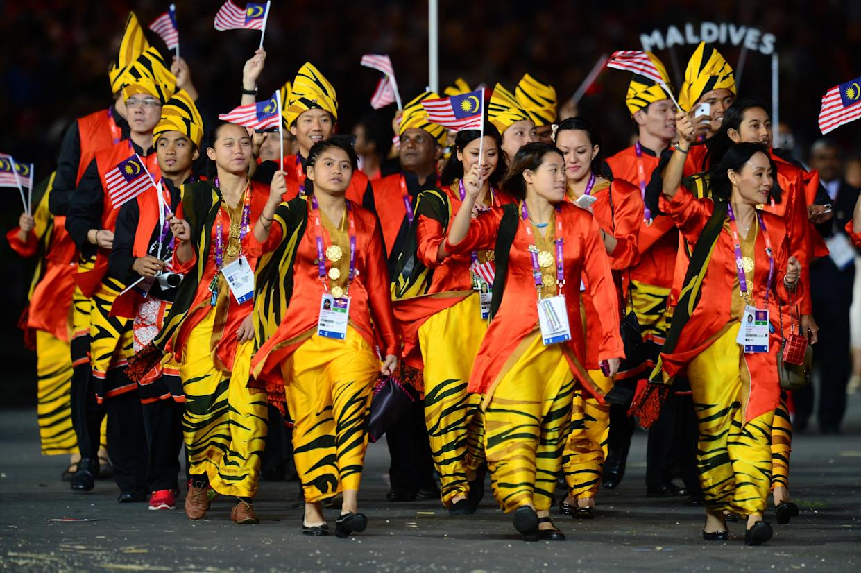 Members of Malaysia's delegation parade during the opening ceremony of the London 2012 Olympic Games in the Olympic Stadium in London on July 27, 2012.     AFP PHOTO / OLIVIER MORIN        (Photo credit should read OLIVIER MORIN/AFP/GettyImages)