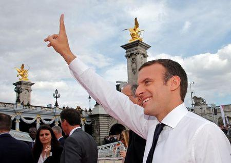 French President Emmanuel Macron waves to the crowd in Paris, France, June 24, 2017. The French capital is transformed into a giant Olympic park to celebrate International Olympic Days with a variety of sporting events for the public across the city during two days as the city bids to host the 2024 Olympic and Paralympic Games.REUTERS/Jean-Paul Pelissier