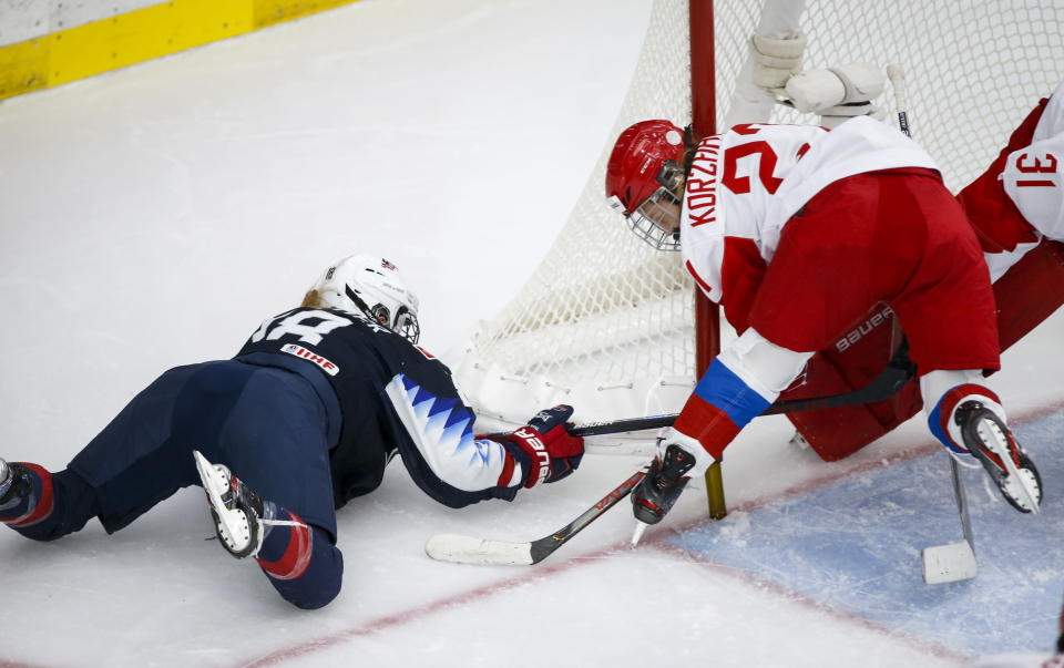 Russia's Veronika Korzhakova, right, crashes into the net after a check from Jesse Compher, of the United States, during second period IIHF Women's World Championship hockey action in Calgary, Alberta, Tuesday, Aug. 24, 2021. (Jeff McIntosh/The Canadian Press via AP)