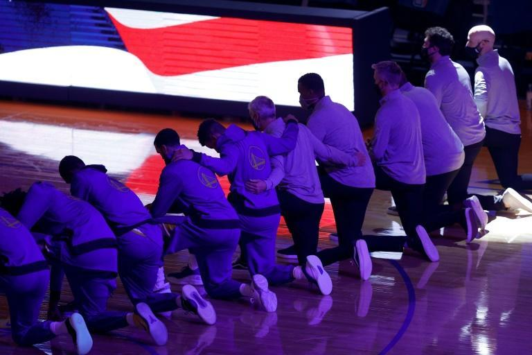 The Golden State Warriors kneel for the National Anthem before their NBA game against the LA Clippers
