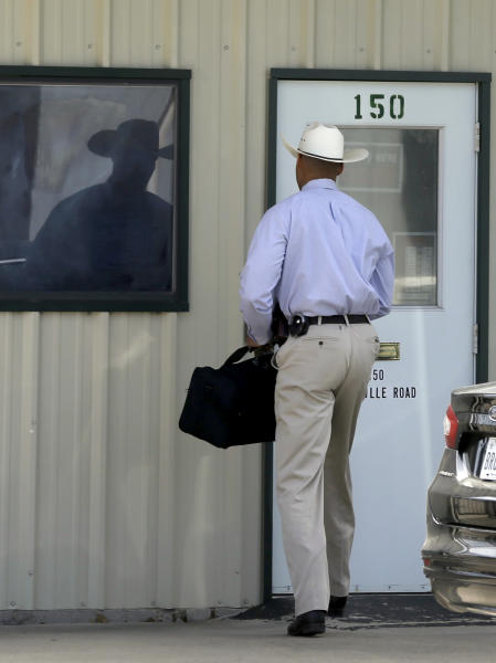 A law enforcement officer, left, walks into the office of Gibson Self Storage where he met with property manager Larry Mathis on Monday, April 15, 2013, in Seagoville, Texas. The facility was searched over the weekend by authorities in addition to the home of Eric Lyle Williams. Texas authorities investigating the killings of a district attorney and his wife are working to build a case against a former justice of the peace prosecuted last year by the slain official's office, a law enforcement official said Monday. (AP Photo/Tony Gutierrez)