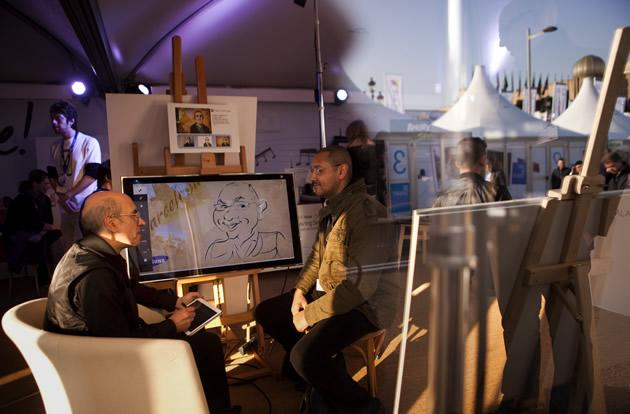 Artist Pedro Jose Espinosa, left, draws visitor Stephane Payet, right, on a Samsung Galaxy.