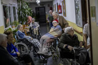 Manuel Alguacil pushes the wheelchair of her wife Carmen Riaza at an elderly care home in Pozuelo de Alarcon, outskirts of Madrid, Thursday, Dec. 24, 2020. Many of the elderly in the residence haven't celebrate Christmas eve with their relatives to prevent the spread of coronavirus (AP Photo/Bernat Armangue)