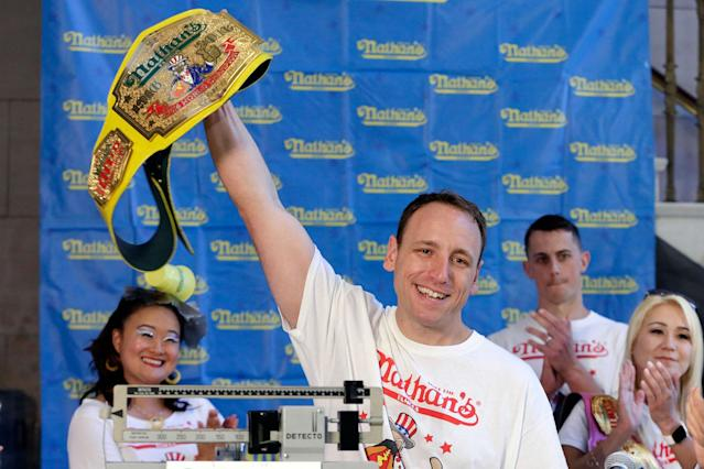 <p>Eight-time men's champion Joey Chestnut, of San Jose, Calif., holds holds his championship belt during the weigh-in for the 2017 Nathan's Hot Dog Eating Contest, in Brooklyn Borough Hall, in New York, Monday, July 3, 2017. Chestnut weighed-in at 221.5 pounds. The current women's champ, Miki Sudo, of Las Vegas, is at right. (AP Photo/Richard Drew) </p>