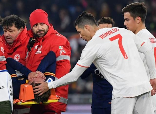 Juventus star Cristiano Ronaldo (r) comforts Nicolo Zaniolo as he is stretchered off the pitch in tears at the Stadio Olimpico. (AFP Photo/Andreas SOLARO)