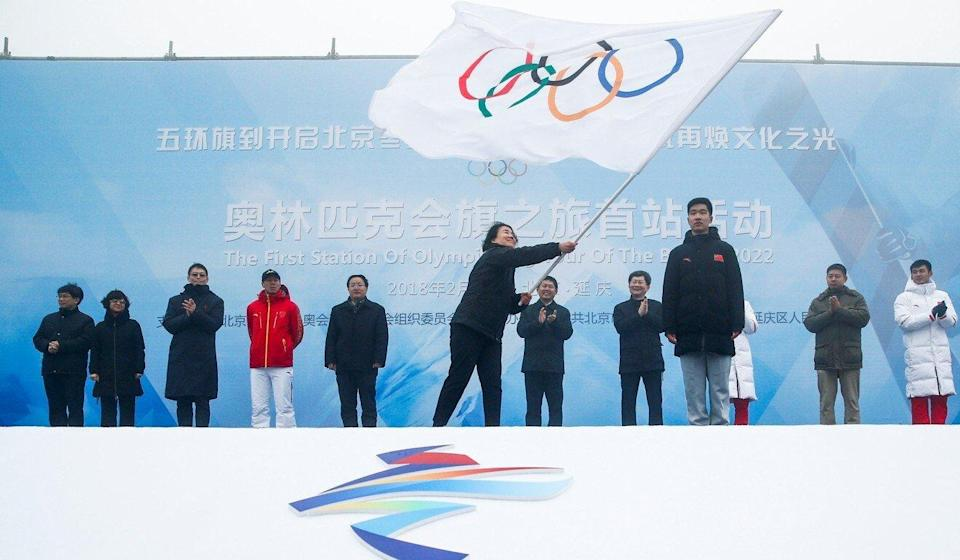 Han Zirong, secretary general of the Beijing Organising Committee for the 2022 Winter Games, waves the Olympic flag during a handover ceremony in Beijing in 2018. Photo: Reuters