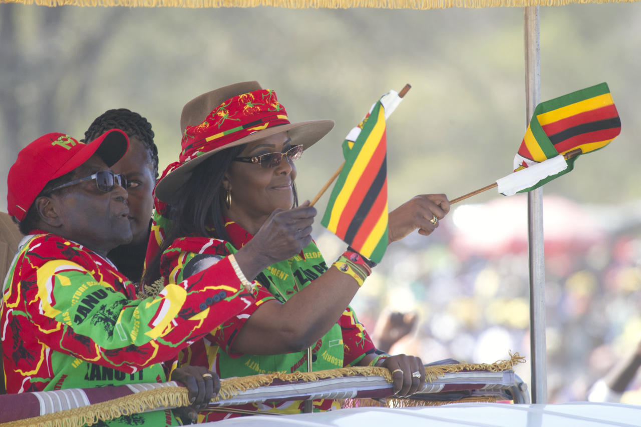 Zimbabwe President Robert Mugabe and his wife Grace wave the Zimbabwean flag while greeting supporters at a rally in Lupane about 170 Kilometres north of Bulawayo, Friday, July 21, 2017. Mugabe's rally is his first since his return from a routine medical review in Singapore. The world's oldest leader has launched a series of rallies targeting the youth ahead of Presidential elections set for 2018. (AP Photo/Tsvangirayi Mukwazhi)