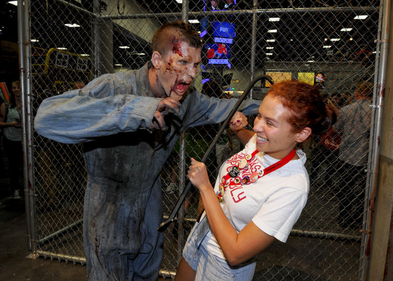 Olivia D'Agostino pulls a away from a zombie at AMC's Walking Dead booth during the Preview Night event on Day 1 of the 2013 Comic-Con International Convention on Wednesday, July 17, 2013 in San Diego. (Photo by Denis Poroy/Invision/AP)