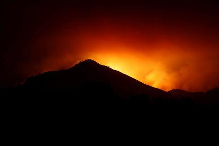 A hill is being silhouetted by flames during the Nuns Fire in Kenwood, California
