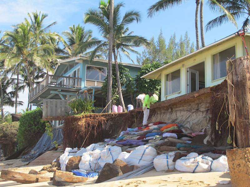 Sandbags are piled up in front of properties damaged by severe beach erosion in the Rocky Point neighborhood of Oahu's North Shore in Haleiwa, Hawaii on Tuesday, Dec. 31, 2013. Some property owners want to be able to install a seawall or something similar to protect their property, but scientists say doing so could lead the sand on the nearby coastline _ including Sunset Beach, home to some of the world's top surfing contests _ to disappear. (AP Photo/Audrey McAvoy)