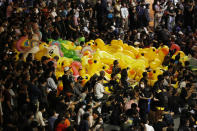 Inflatable yellow ducks, a common symbol of the protest movement, are floated through a crowd of anti-government protesters attending a rally Wednesday, Dec. 2, 2020 in Bangkok, Thailand. Thailand's highest court has acquitted Prime Minister Prayuth Chan-ocha of breaching ethics clauses in the country's constitution, allowing him to stay in his job. (AP Photo/Sakchai Lalit)