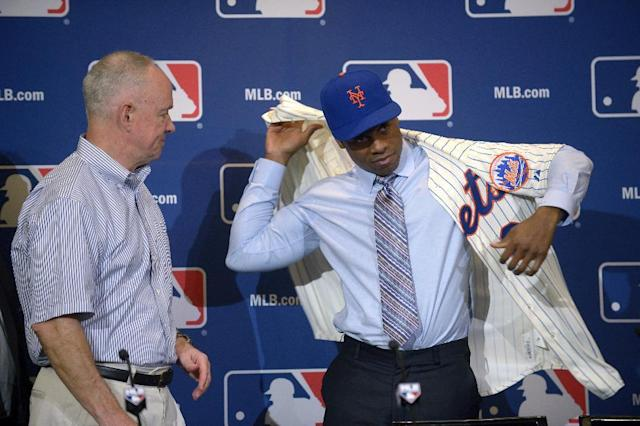 New York Mets general manager Sandy Alderson, left, watches as their newest outfielder Curtis Granderson puts on a jersey after being introduced during a news conference at baseball's winter meetings in Lake Buena Vista, Fla., Tuesday, Dec. 10, 2013.(AP Photo/Phelan M. Ebenhack)