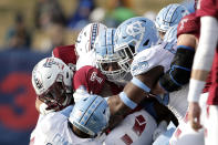 Temple running back Re'Mahn Davis, left, is grabbed by North Carolina defenders during the second half of the Military Bowl NCAA college football game, Friday, Dec. 27, 2019, in Annapolis, Md. (AP Photo/Julio Cortez)
