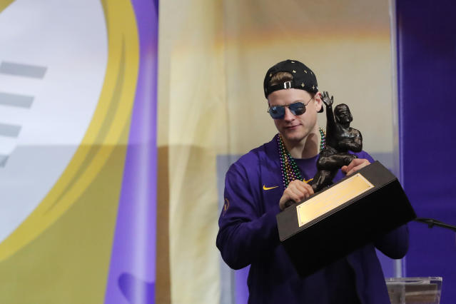 LSU quarterback Joe Burrow holds the Heisman Trophy that is being presented to the school during a celebration of their NCAA college football championship, Saturday, Jan. 18, 2020, on the LSU campus in Baton Rouge, La. (AP Photo/Gerald Herbert)