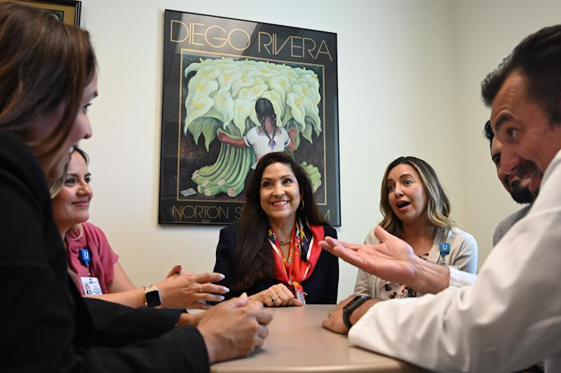 Cynthia Telles, director of the University of California, Los Angeles' Hispanic Neuropsychiatric Center of Excellence, (center) conducts an informal staff meeting in her office.