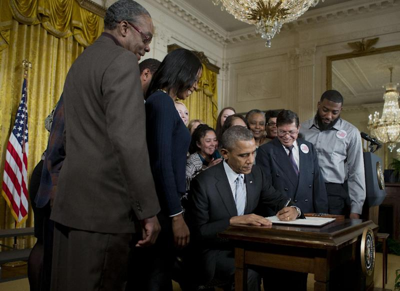 President Barack Obama, surrounded by workers, signs an executive order to raise the minimum wage for federal contract workers, Wednesday, Feb. 12, 2014, during a ceremony in the East Room of the White House in Washington. Wage increase to $10.10 an hour, goes into effect next year, and applies to new contracts and replacements for expiring contracts. (AP Photo/Pablo Martinez Monsivais)