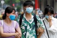 People wear protective masks as they walk down a street in Hanoi