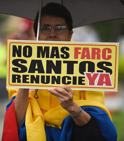 """A woman holds a sign reading """"No more FARC. Santos resign now"""" during the """"No More"""" march against the government of President Juan Manuel Santos and the Revolutionary Armed Forces of Colombia (FARC) guerrillas in Cali (AFP Photo/Luis Robayo)"""