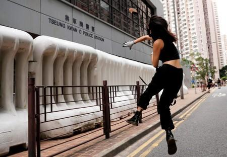 FILE PHOTO: An anti-extradition bill protester throws a stone at a police station in Tseung Kwan O residential district, in Hong Kong
