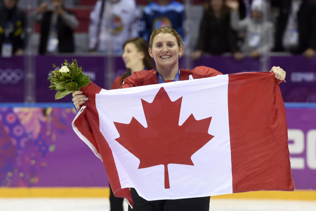 "FILE - In this Feb. 21, 2014, file photo, Canada's Hayley Wickenheiser celebrates with the Canadian flag after beating the USA 3-2 in overtime at the Sochi Winter Olympics in Sochi, Russia. With a laugh, Kim Pegula's competitive nature kicked in when the subject of the Toronto Maple Leafs hiring Hayley Wickenheiser was broached. Impressed as the Sabres president was by the gender-breaking move in August, Pegula's first reaction was wondering how Buffalo's cross-border rival beat her to the punch in making Wickenheiser the NHL's first female to hold a hockey operations role as assistant director of player development. ""Darn it,"" Pegula said, smiling. ""I wish I would've done it first."" (AP Photo/Paul Chiasson, The Canadian Press, File)"