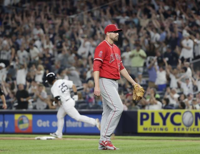 Los Angeles Angels relief pitcher Jim Johnson, right, waits as New York Yankees' Gleyber Torres (25) runs the bases after hitting a home run during the seventh inning of a baseball game Friday, May 25, 2018, in New York. (AP Photo/Frank Franklin II)