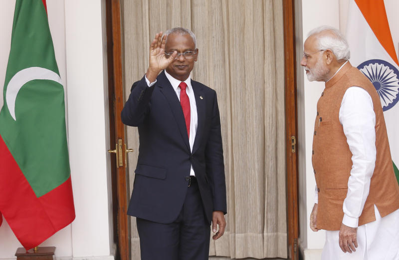 Indian Prime Minister Narendra Modi, right, watches as Maldives President Ibrahim Mohamed Solih waves to media before their meeting in New Delhi, India, Monday, Dec. 17, 2018. Solih is on a three-day visit to India. (AP Photo/Manish Swarup)
