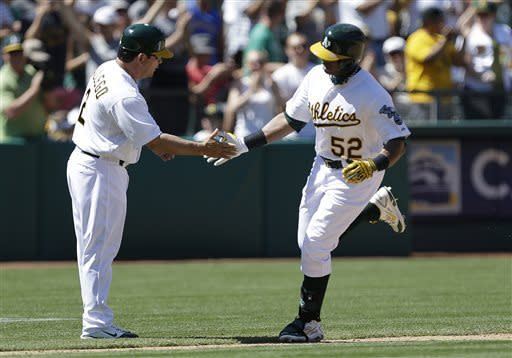 Oakland Athletics' Yoenis Cespedes, right, is congratulated by third base coach Mike Gallego after hitting a home run off Kansas City Royals' Kelvin Herrera in the eighth inning of a baseball game on Sunday, May 19, 2013, in Oakland, Calif. (AP Photo/Ben Margot)