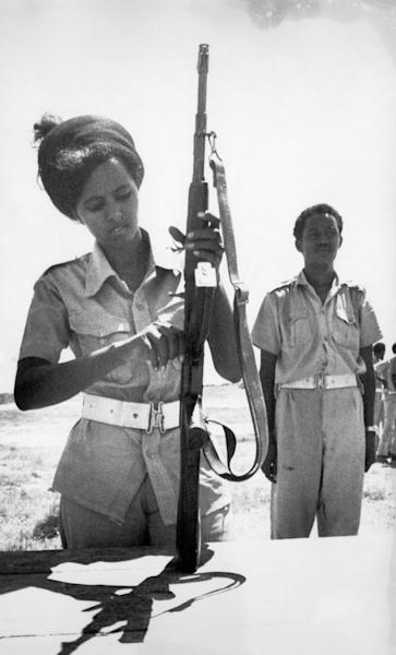 FILE - In this Feb. 25, 1978 file photo, a Somali Army female recruit checks her automatic weapon at a military training camp in Halane, Mogadishu. At right is her instructor. On Friday, Aug. 23, 2019, The Associated Press reported on this photo circulating online, incorrectly identified as showing U.S. Rep. Ilhan Omar, D-Minn., undergoing military training. This black-and-white film image was made before Omar was born. (AP Photo)
