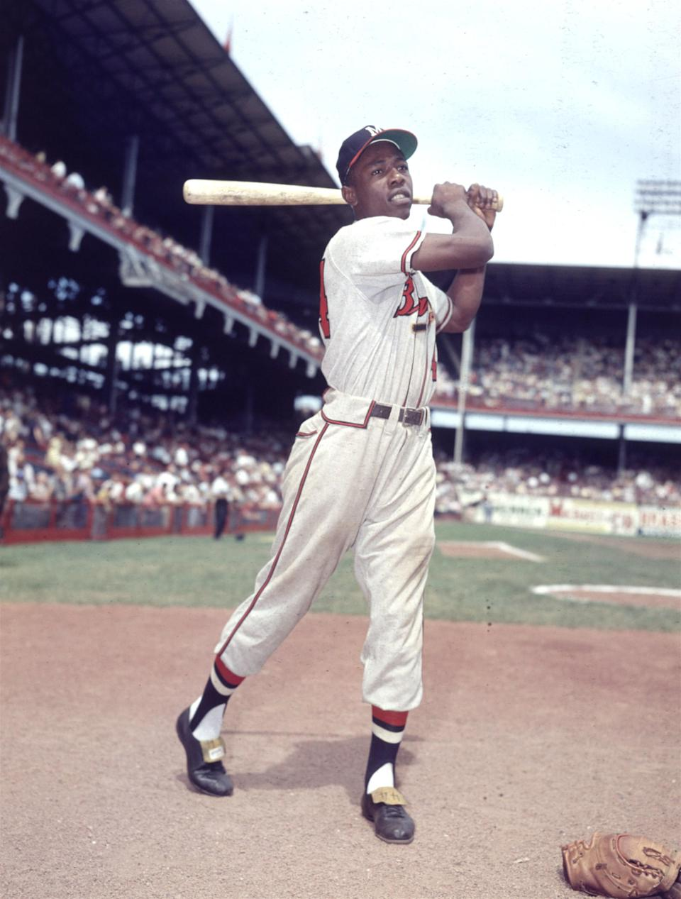 FILE- In this 1954 file photo, Milwaukee Braves' Hank Aaron poses for a photo at Ebbets Field during an exhibition season in New York. Hank Aaron, who endured racist threats with stoic dignity during his pursuit of Babe Ruth but went on to break the career home run record in the pre-steroids era, died early Friday, Jan. 22, 2021. He was 86. The Atlanta Braves said Aaron died peacefully in his sleep. No cause of death was given. (AP Photo, File)